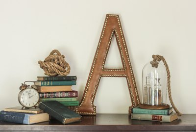 "A large leather ""A"" with nailhead trim, staged with stacked vintage books, glass cloche, and vintage clock."