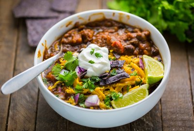 Black Bean and Pumpkin Chili topped with cilantro, tortilla chips, cheddar cheese, and sour cream.