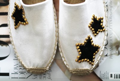 White Espadrilles with Black Suede Stars and Gold Studs on a Stack of Magazines