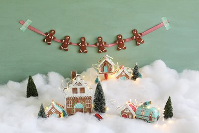 Gingerbread garland hanging above snowy gingerbread village