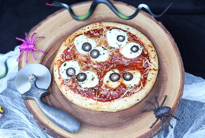 Eyeball pizza served on wood platter