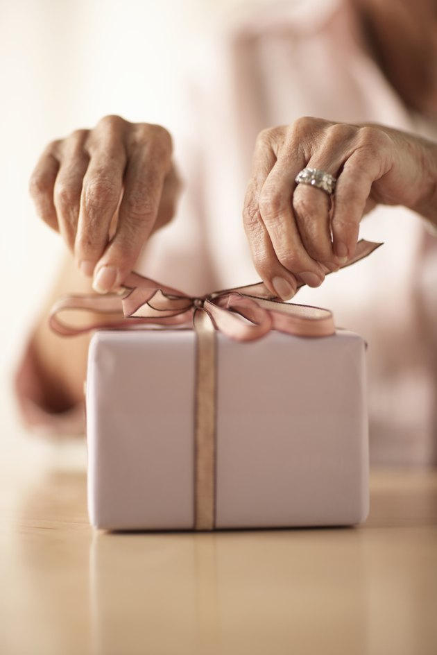 Senior woman tying bow on gift, mid section, close-up of hands