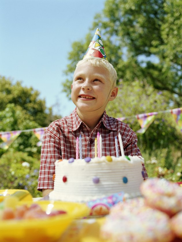 Boy (6-8) sitting outdoors by birthday cake, smiling