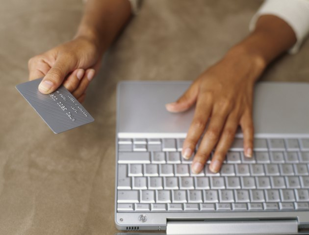 close-up of human hands working on a laptop and holding a credit card