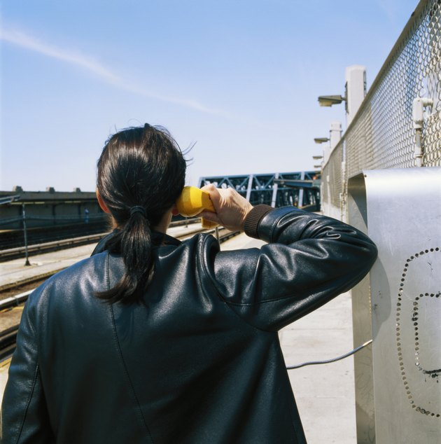 Woman using public telephone at station platform, rear view