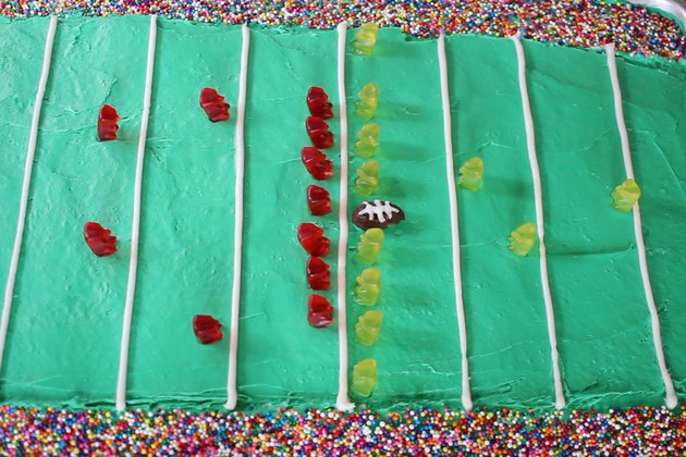 22 gummy bears arranged on football field cake with candy football