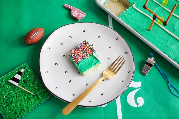 Slice of stadium sheet pan cake on plate with a gold fork