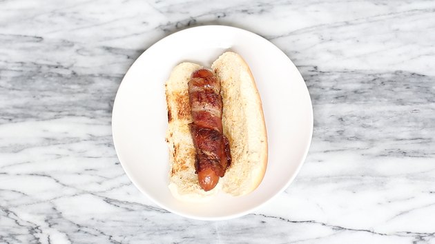 Bacon-wrapped hot dog in toasted side slit bun