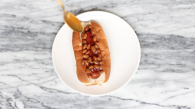 Spooning Boston baked beans on top of hot dog