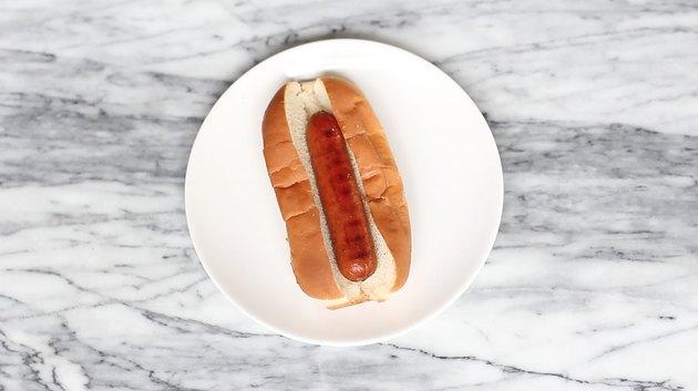Cooked hot dog inside toasted top slit bun
