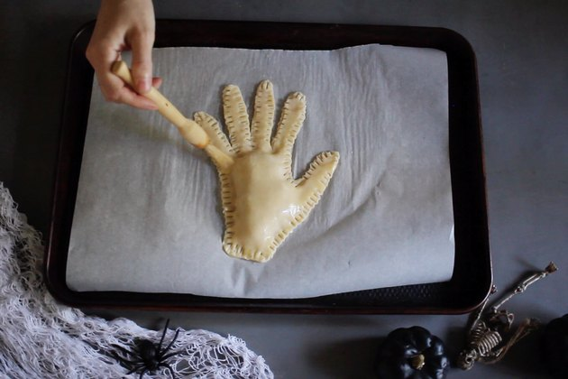 Brushing severed hand pie with egg wash
