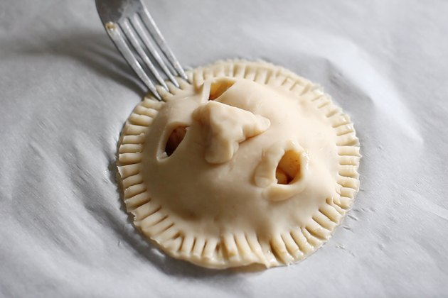 Crimping edges of shrunken head pie with fork