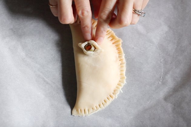 Pressing eye-shaped olive onto calzone