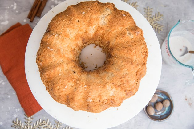 naked bundt cake on a cake stand and measuring cup of glaze