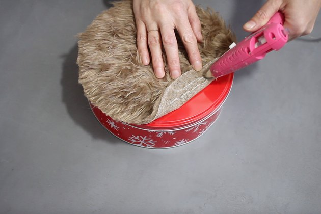 Gluing brown fur to cookie tin