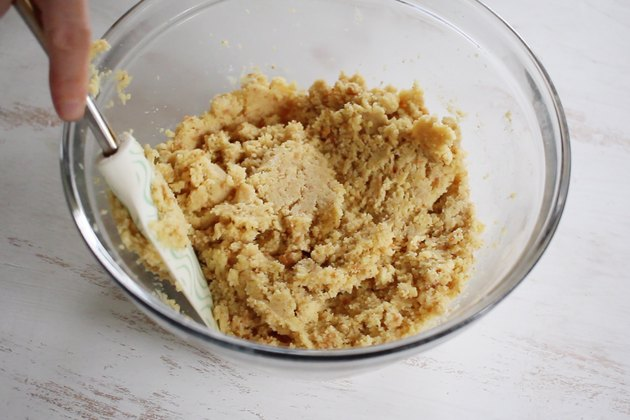Stirring frosting into cake crumbs to form batter