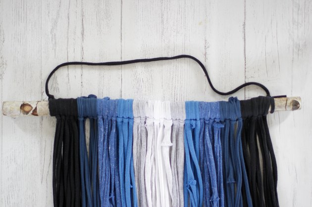 Grab some old t-shirts hanging around in your closet to create an eye-catching and stylish wall hanging.