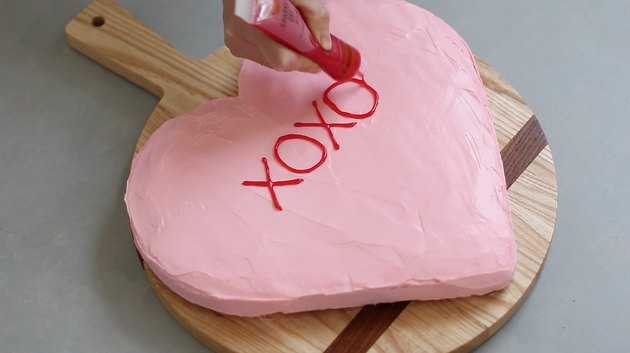 "Writing ""XOXO"" on cake"