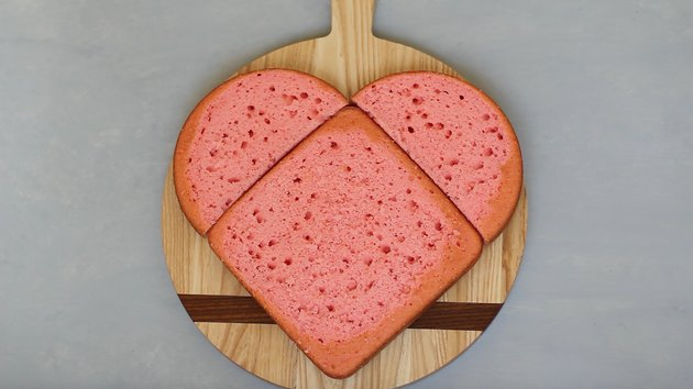 Round cake halves placed above square cake in heart shape