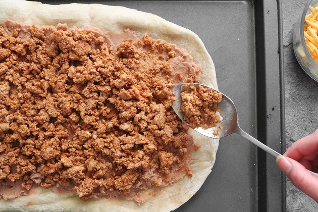Add refried beans and taco meat