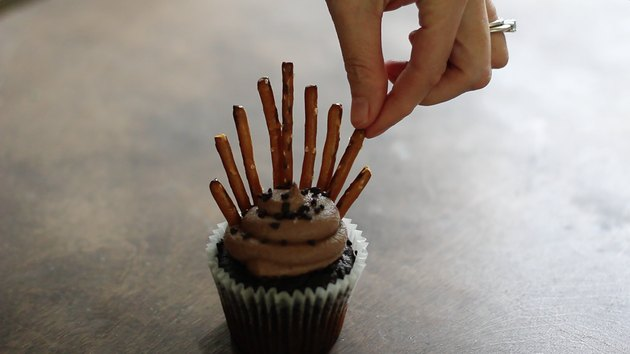 Inserting pretzel sticks into cupcake