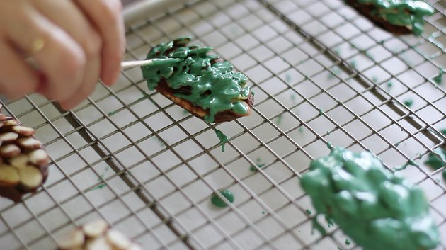 Smoothing melted green candy onto almonds