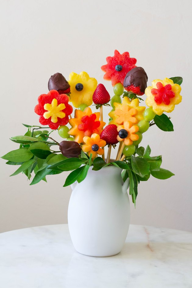 DIY edible fruit flower arrangement in white vase on table