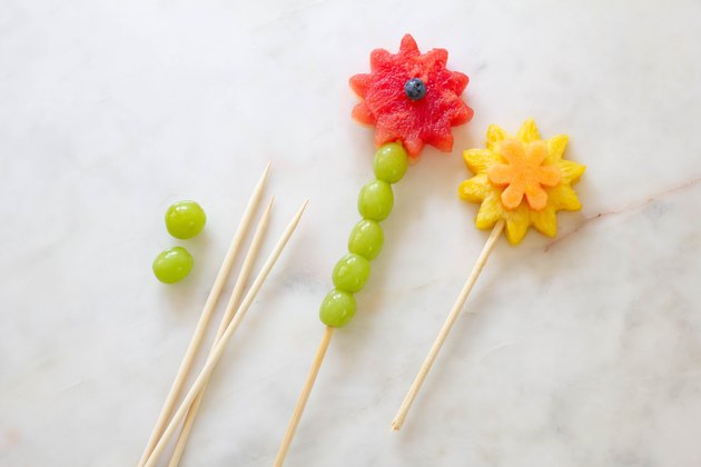 Fruit flowers and green grapes inserted onto wood skewers
