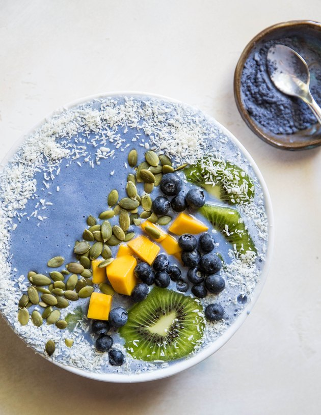 Blue smoothie bowl with fruit and seeds on top