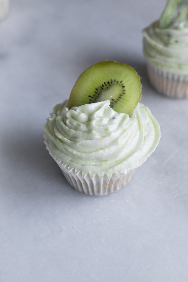 Generously frost the cupcakes and top with a kiwi slice.