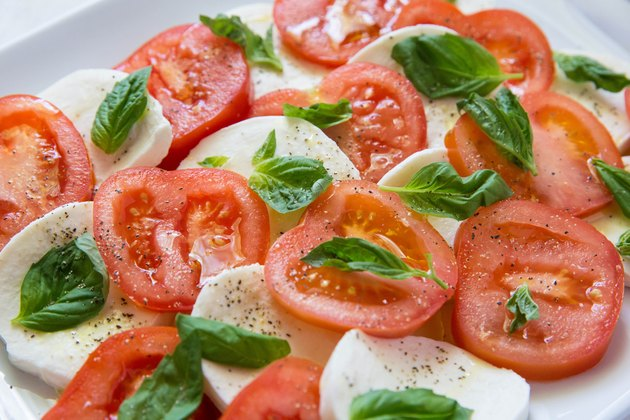 tomatoes and mozzarella on a platter with salt, pepper, and basil