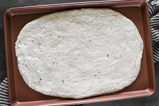 Spread pizza crust on baking sheet