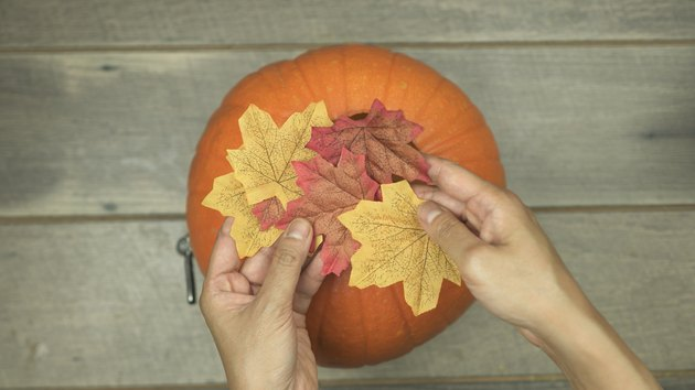Decorating DIY Pumpkin Keg with fabric leaves