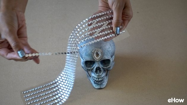 Applying gemstone strips to plastic skull for DIY Gemstone Studded Halloween Skull