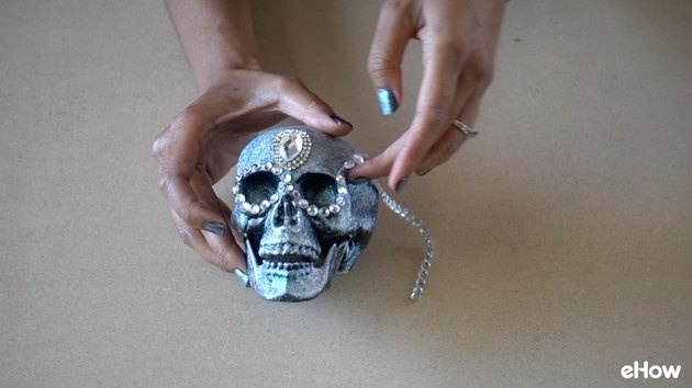 Applying gemstone strip around eyes of plastic skull for DIY Gemstone Studded Halloween Skull