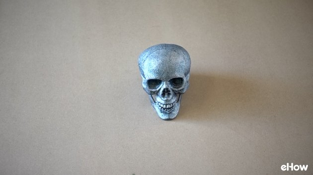 Plastic skull painted with glitter spray paint.
