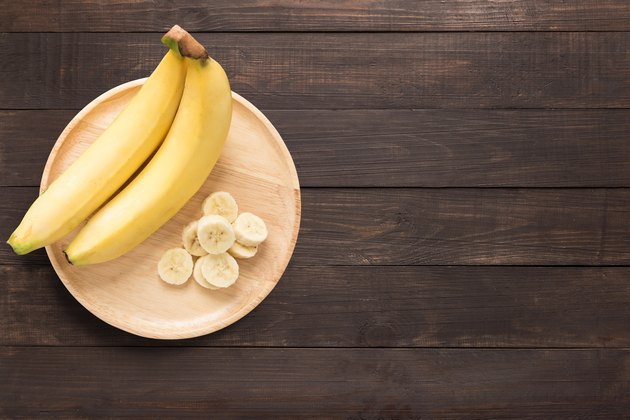 Bananas in a wooden dish on a wooden background.