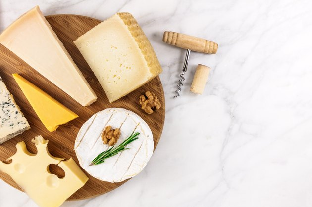 Selection of cheeses with corkscrew, cork, and copyspace