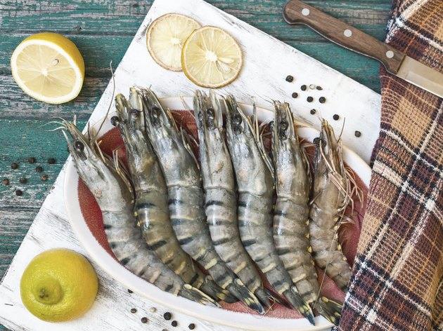 Fresh raw tiger prawns and spices on wooden table