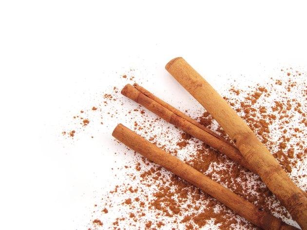Cinnamon sticks with powder on white