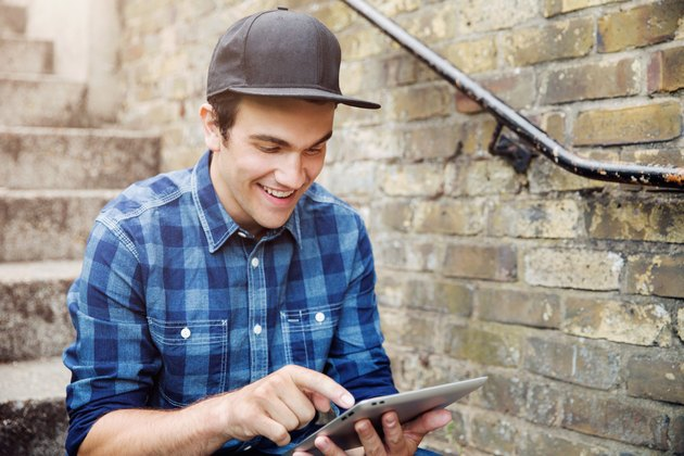 Young man sat on steps with tablet.