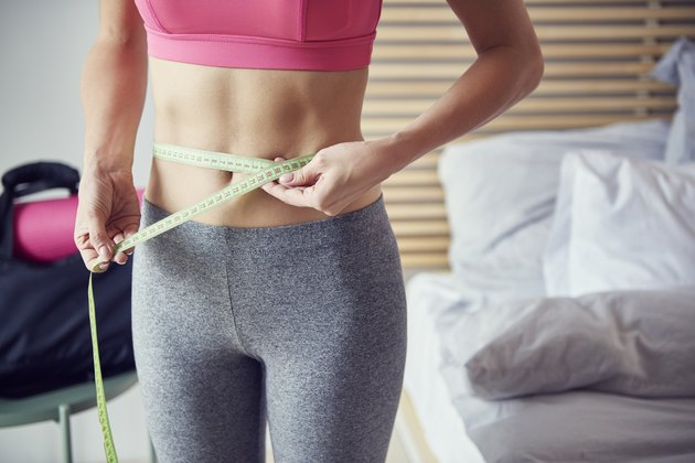 Slim woman with measuring tape at home