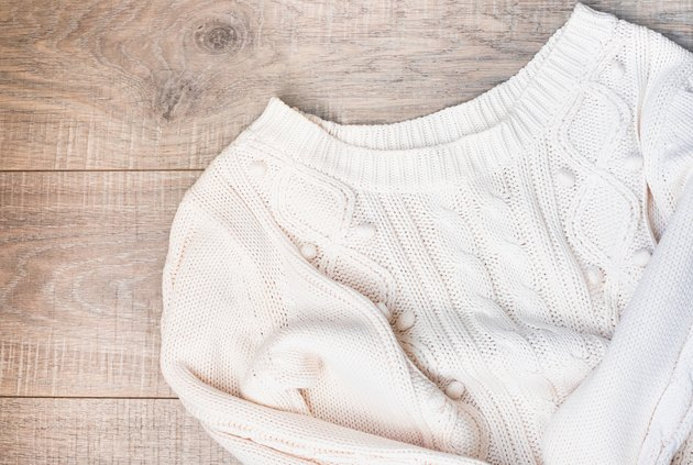 Women's autumn, winter clothes - white knitted pullover oversize, top view. Flat lay.
