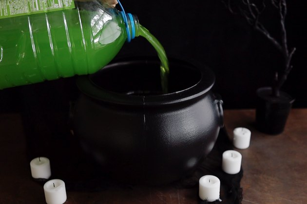 Pouring green punch into black cauldron