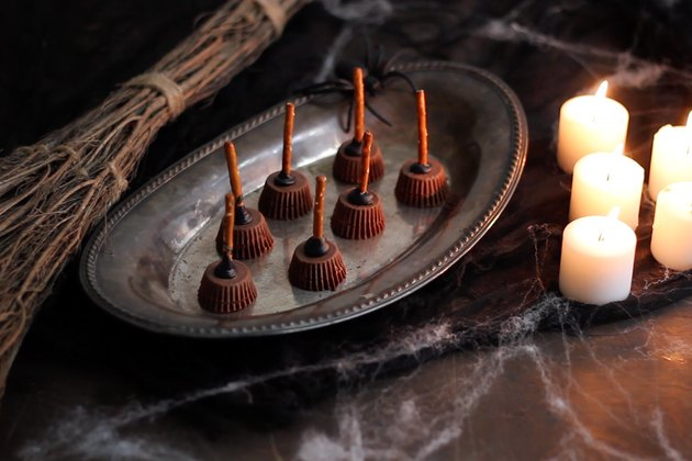 DIY witches broom desserts made from peanut butter cups and pretzels