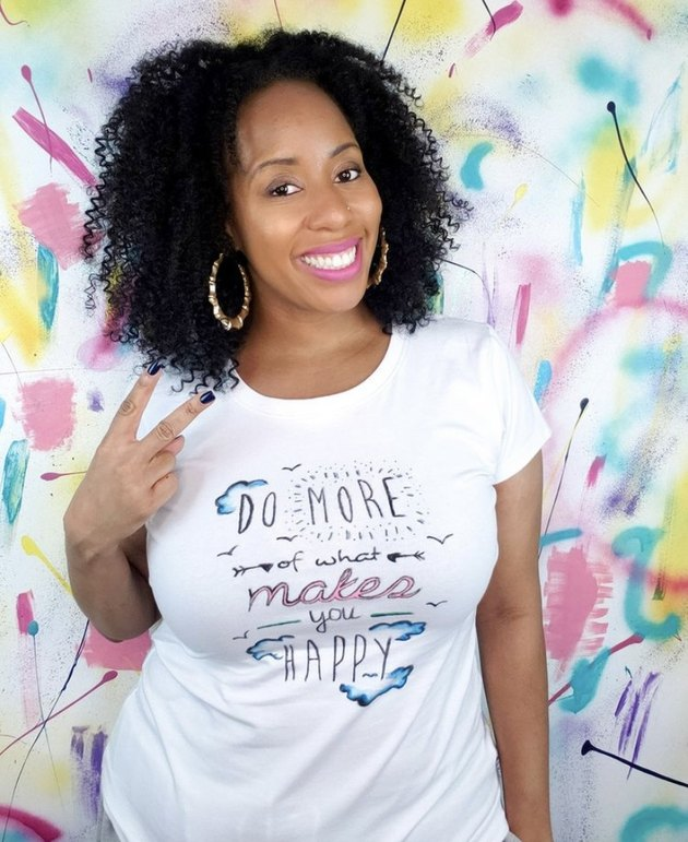 A.V. poses in a white t-shirt.