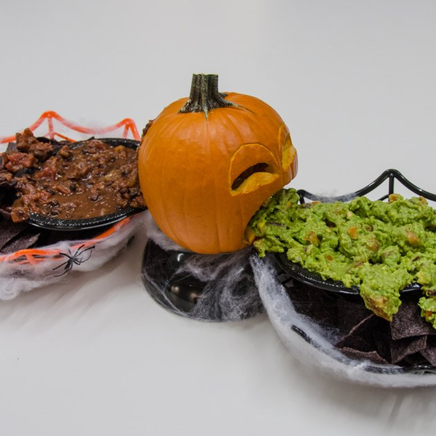 Small pumpkin with guacamole on one side and salsa on the other