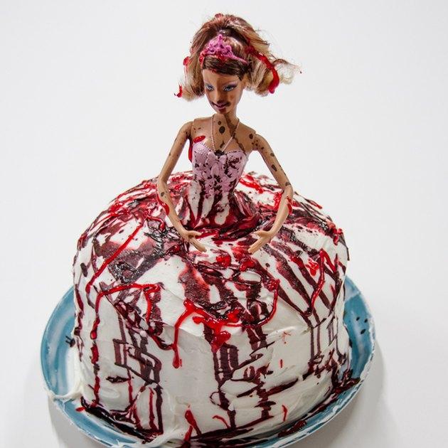 Barbie doll standing in center of blood-splattered cake.