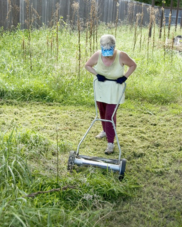 Woman trying to mow yard with manual mower