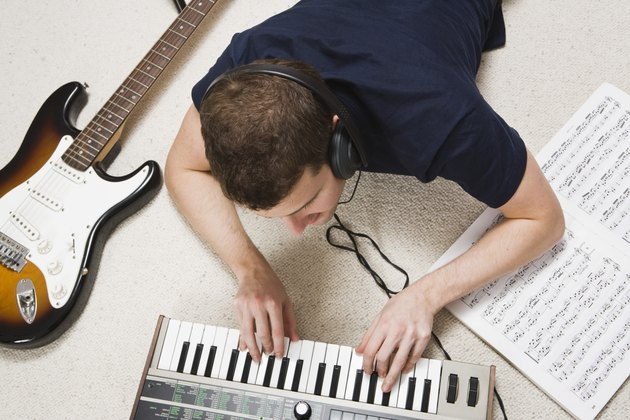 Man playing piano keyboard with headphones